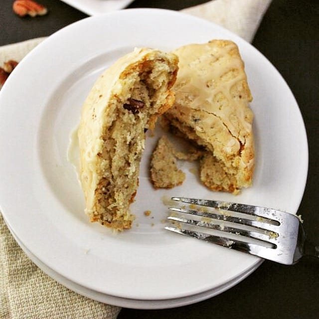 scone cut in half on a white plate with a fork