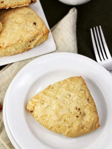 maple pecan scones on white plates with a fork, pecans, and napkin