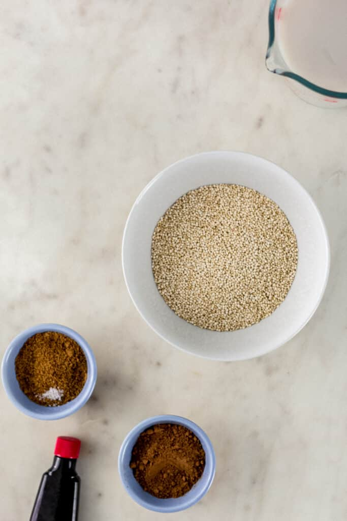 ingredients for chocolate quinoa in small bowls on marble surface