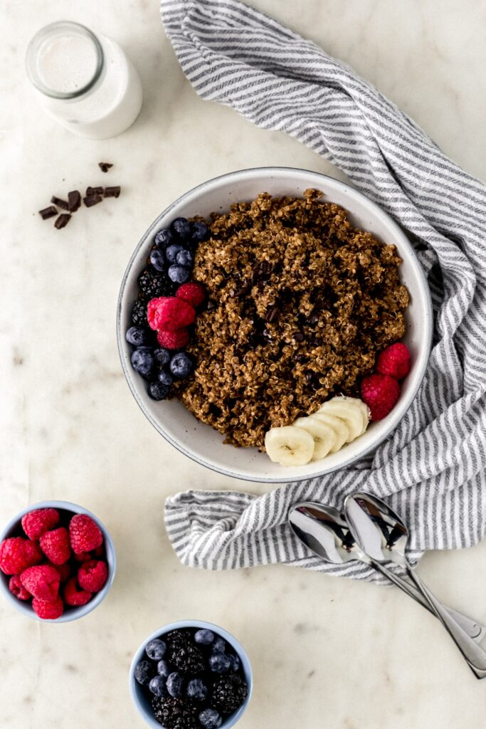 overhead view with chocolate quinoa in white bowl with spoons, cloth napkin, and small bowls with fresh berries.