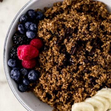 chocolate quinoa in white serving bowl topped with fresh berries, chocolate, and banana.