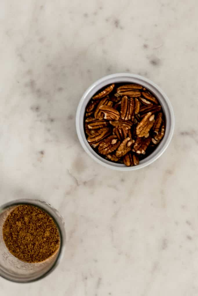 two ingredients needed for candied pecans in jar and white bowl