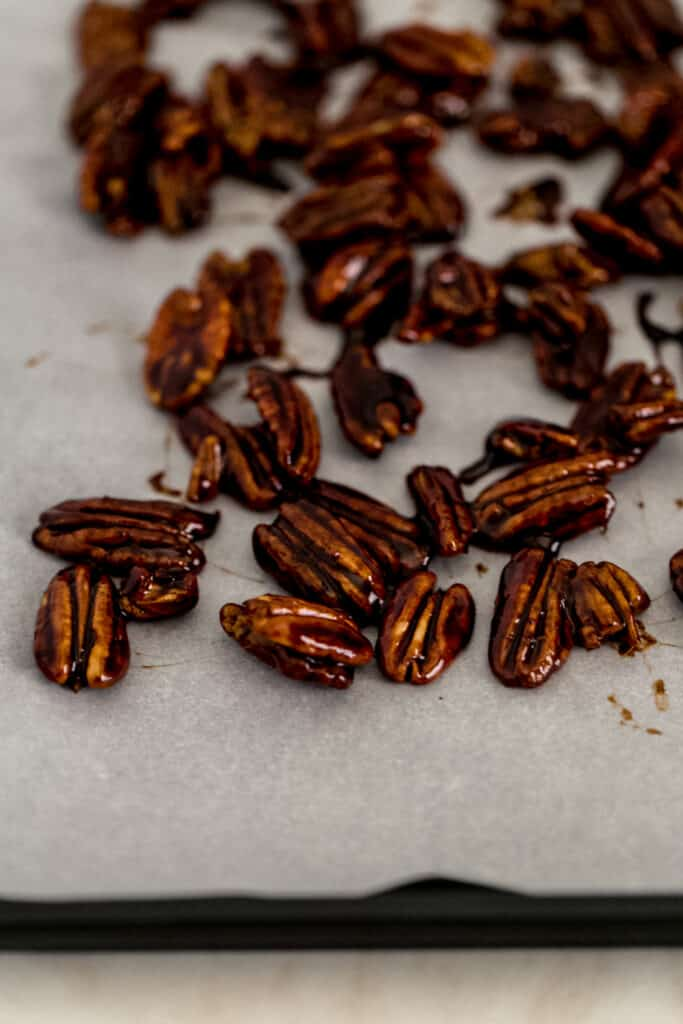 candied pecans on parchment lined baking sheet