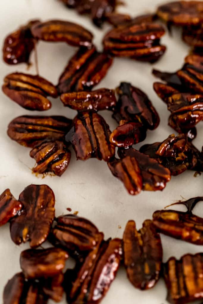 candied pecan on a parchment lined baking sheet