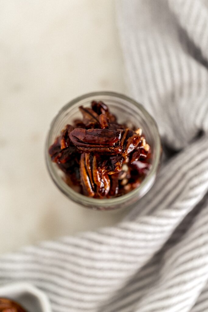 overhead view coconut sugar candied pecans in a small glass jar