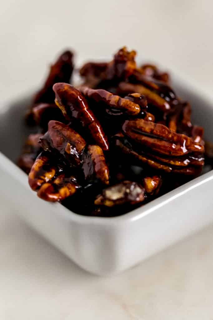 candied pecans in a small white square container