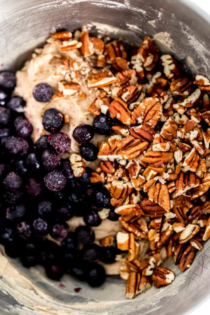 frozen blueberries and chopped pecans added to blueberry coffee cake mixture in stand mixer bowl.