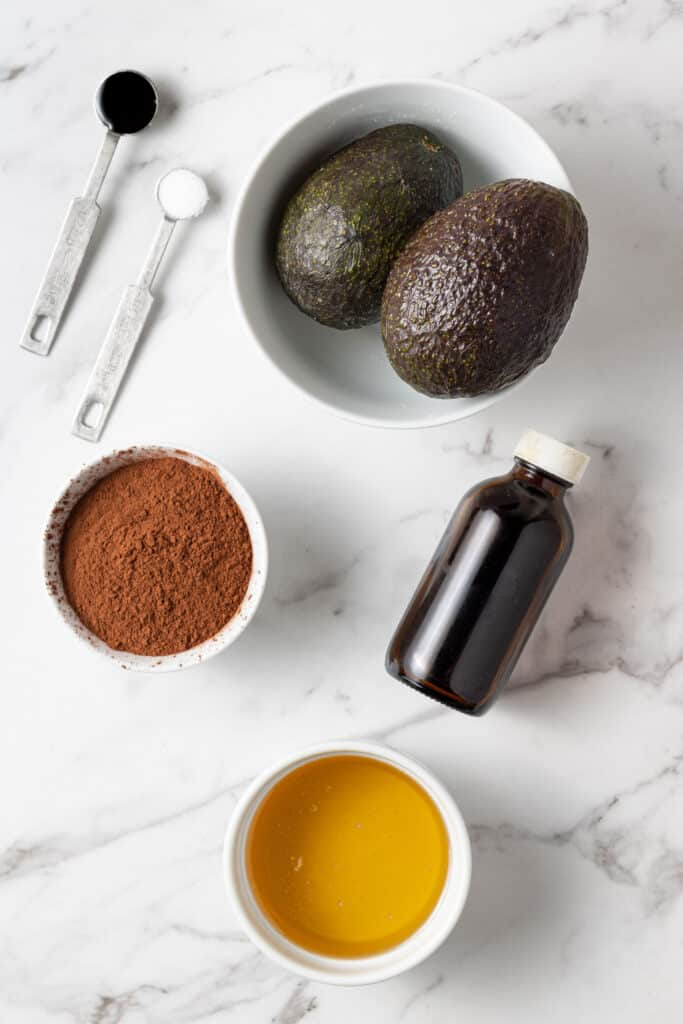ingredients to make chocolate avocado mousse on marble surface.