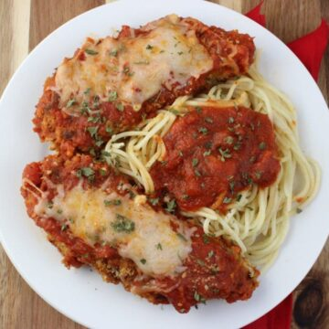 Overhead view of Baked Chicken Mozzarella with spaghetti on plate