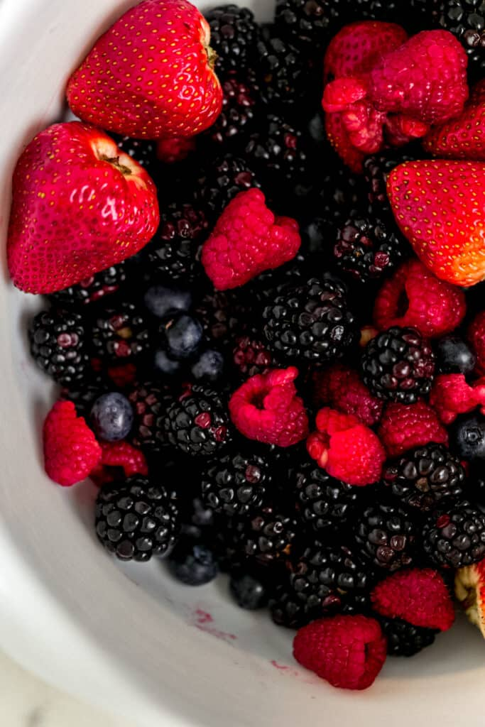 mixture of different kinds of berries in a large white mixing bowl