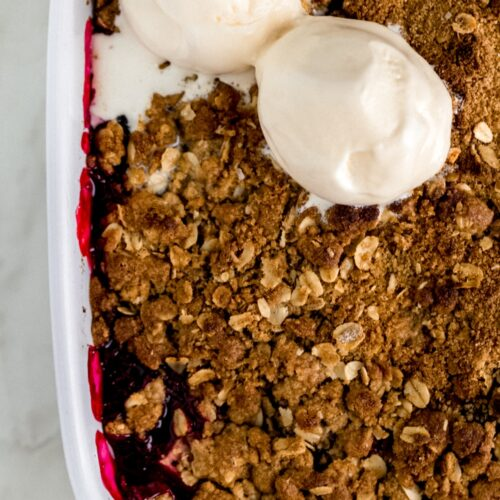 berry crisp in square white baking dish with two scoops of vanilla ice cream on top