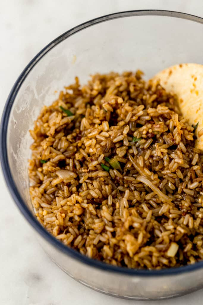 cooked fried brown rice in glass bowl with wooden spoon