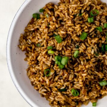 fried brown rice topped with green onion in white serving bowl