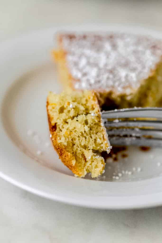 piece of orange olive oil cake on small white plate with fork