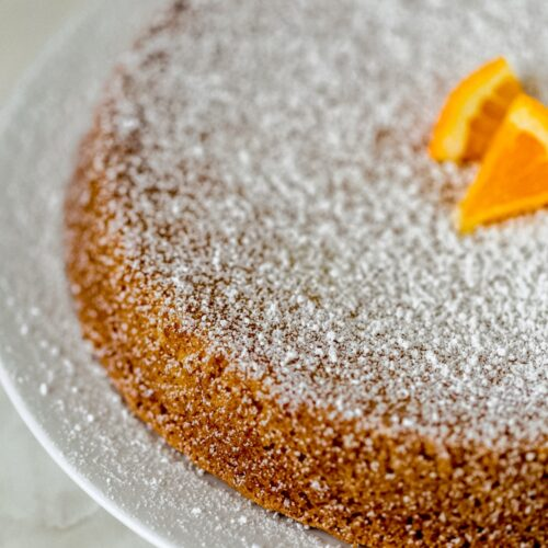 whole olive oil cake on big white plate topped with powdered sugar