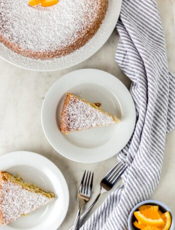 orange olive oil cake on three white plates with forks and napkin
