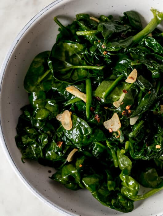 overhead view of sauteed garlic spinach in a large bowl