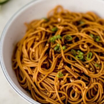 close up side view sesame noodles in white bowl