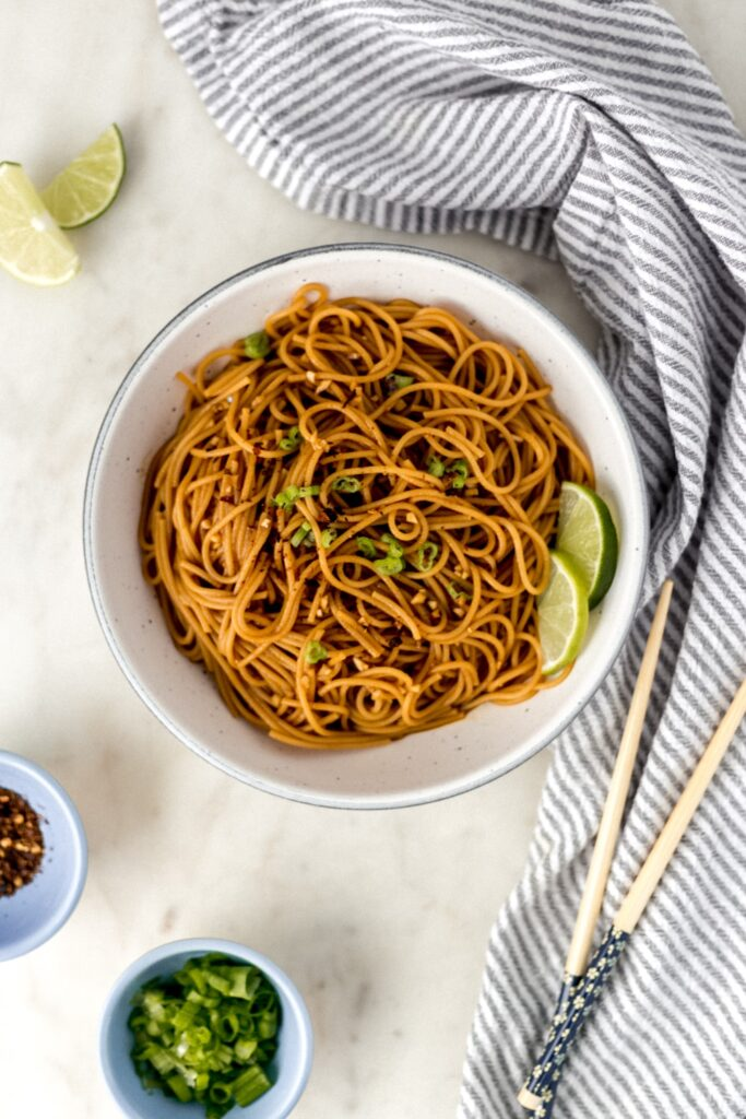 overhead view easy sesame noodles in white bowl with napkin and chop sticks