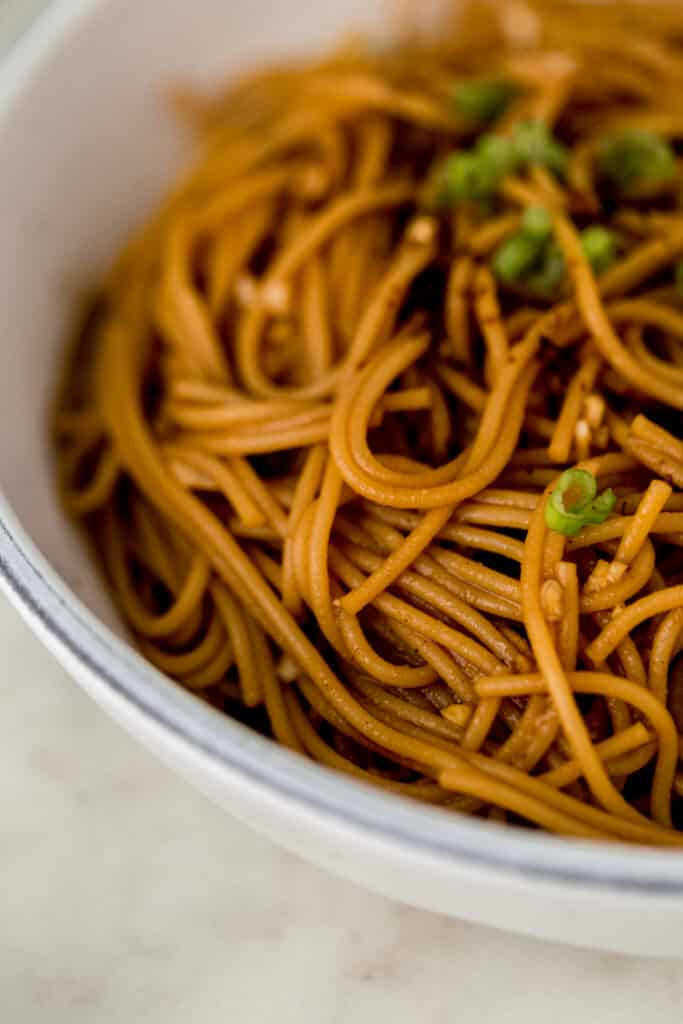 close up side view sesame noodles in large white bowl topped with scallions