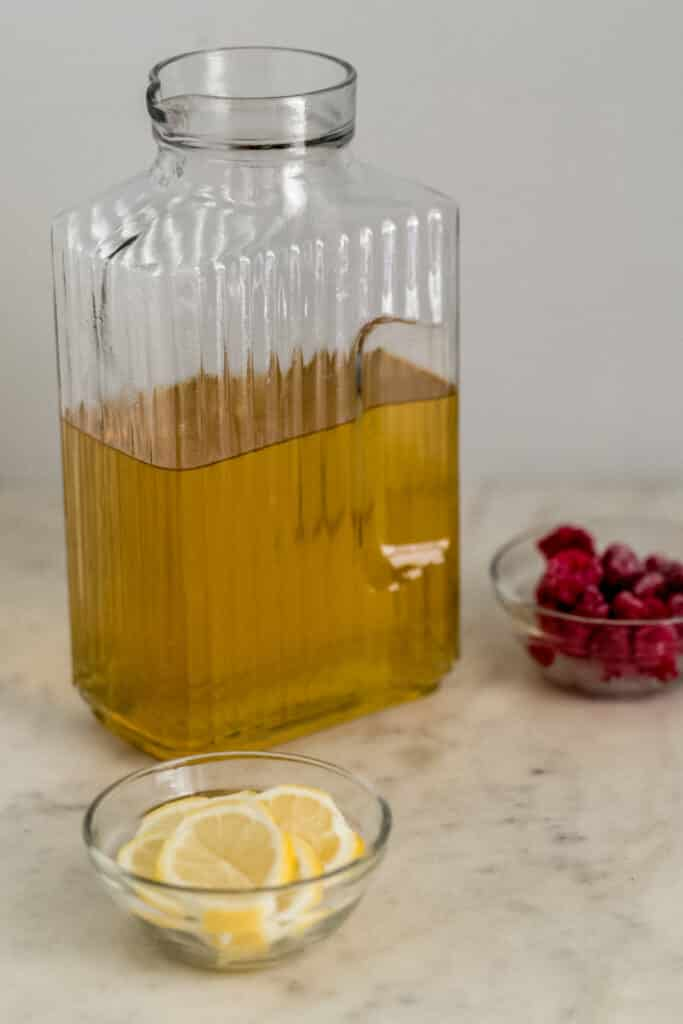 green tea in glass pitcher with small bowls of lemon and raspberries