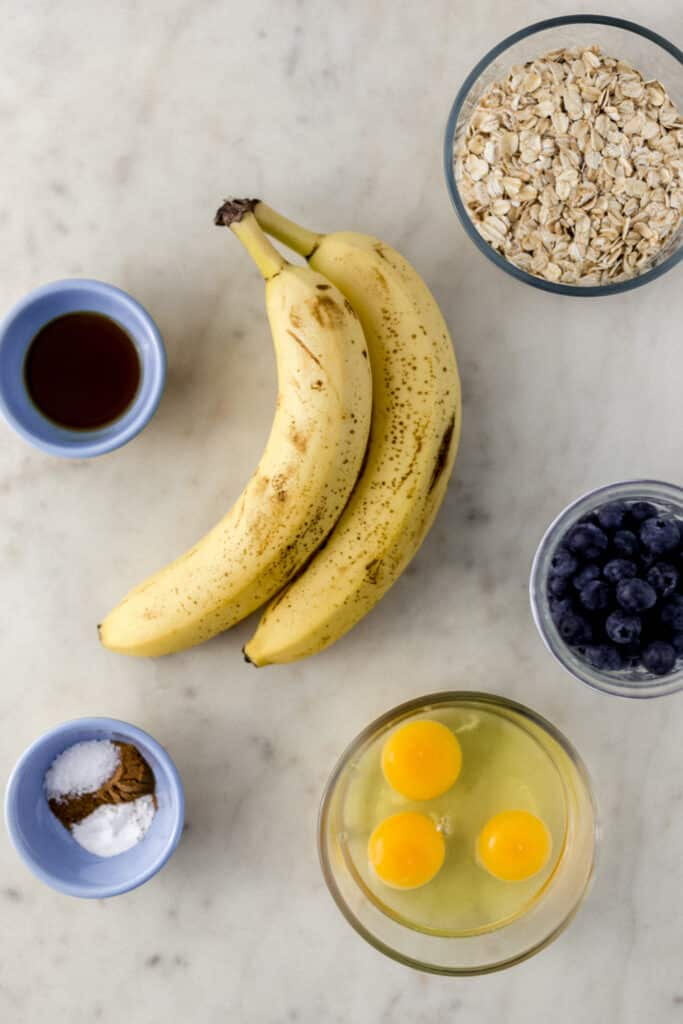 ingredients to make banana pancakes with blueberries on marble surface