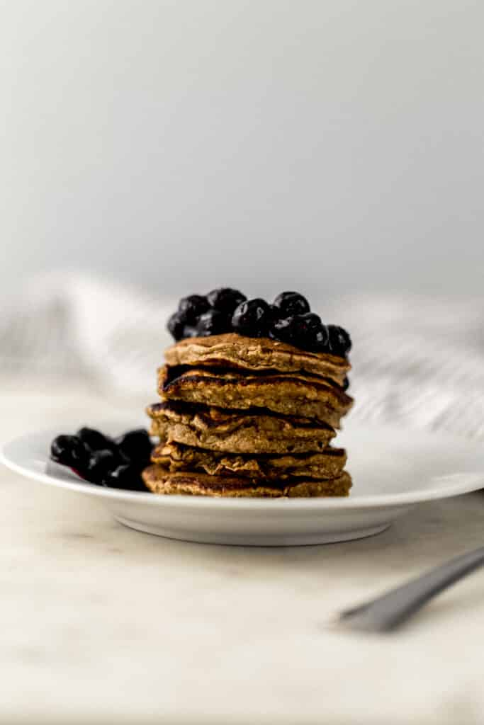 banana pancakes topped with sauteed blueberries on white plate