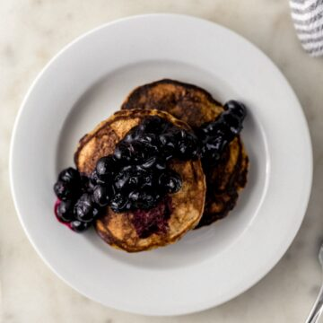 two banana pancakes topped with blueberries on white plate