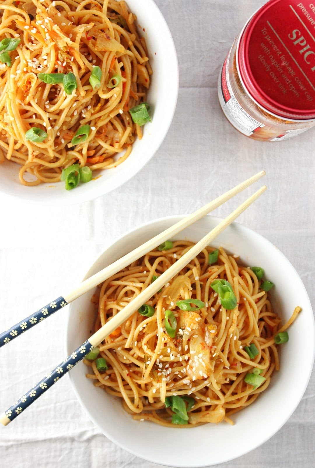 overhead view of kimchi sesame noodles in two bowls with chopsticks