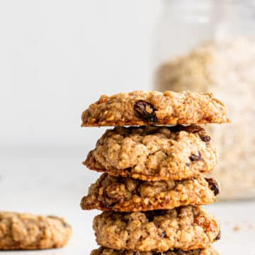 side view of a stack of oatmeal raisin cookies on white surface with glass jar of oats in the background.
