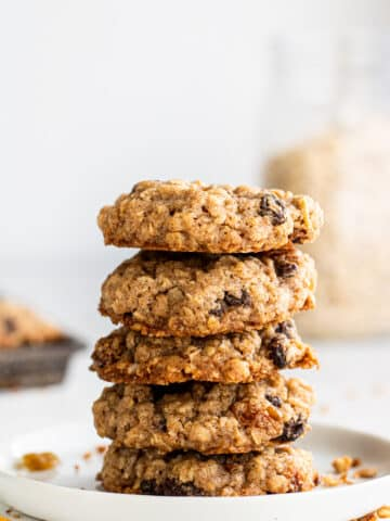 close up side view white plate with a stack of five oatmeal raisin cookies on it.