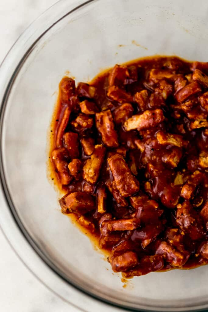 meatless crispy tenders tossed in barbecue sauce in glass mixing bowl.