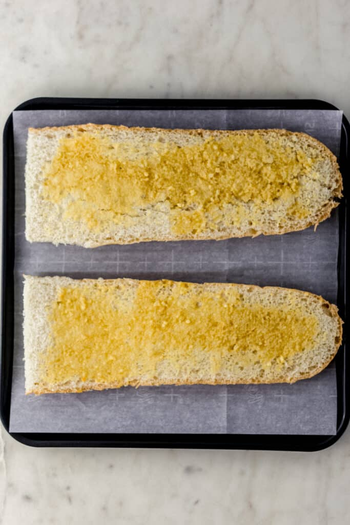 French bread topped with garlic butter mixture before baking on parchment lined baking sheet