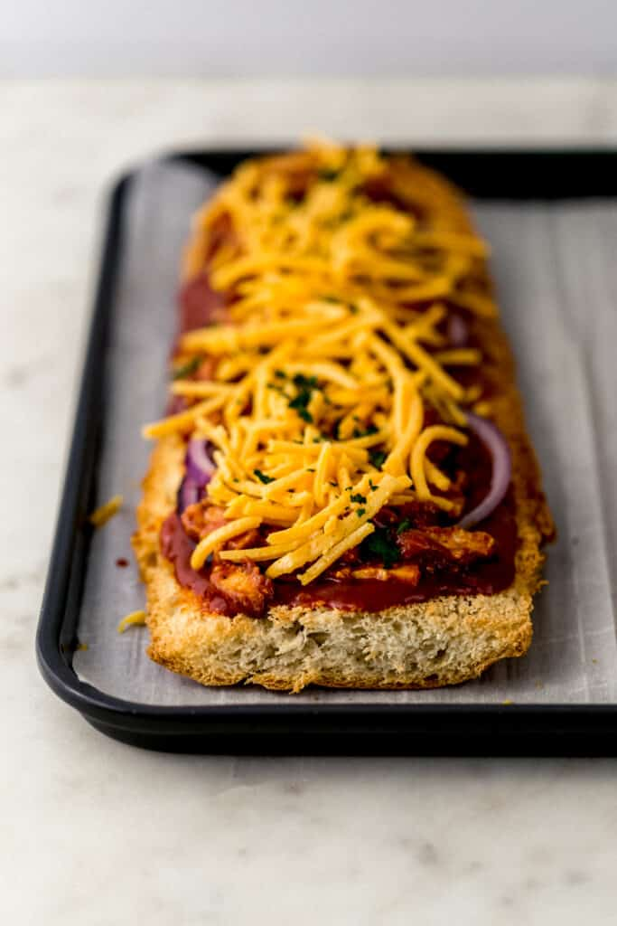 parchment lined baking sheet with barbecue French bread pizza on it before baking.