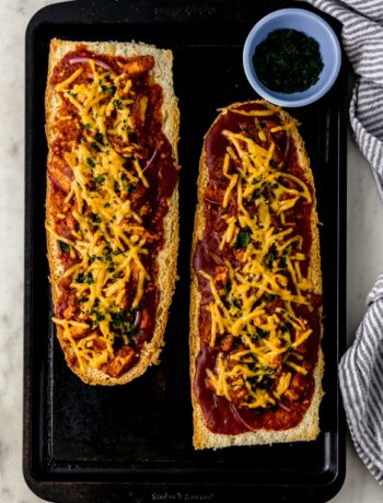 BBQ French bread pizza on baking sheet next to cloth napkin