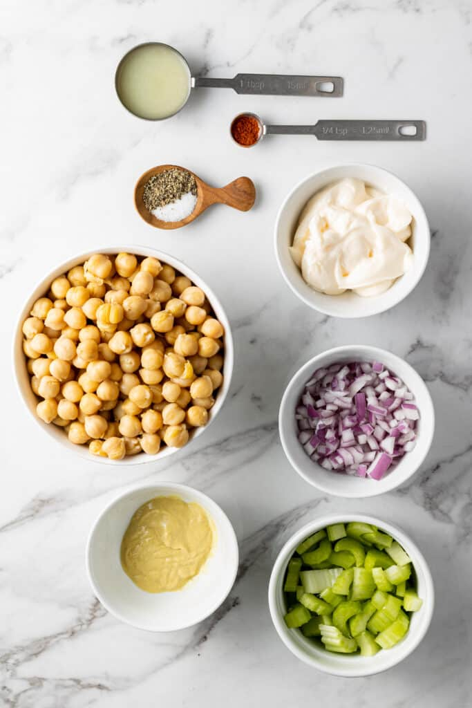 overhead view of all the ingredients needed to make chickpea salad in separate containers on marble surface.