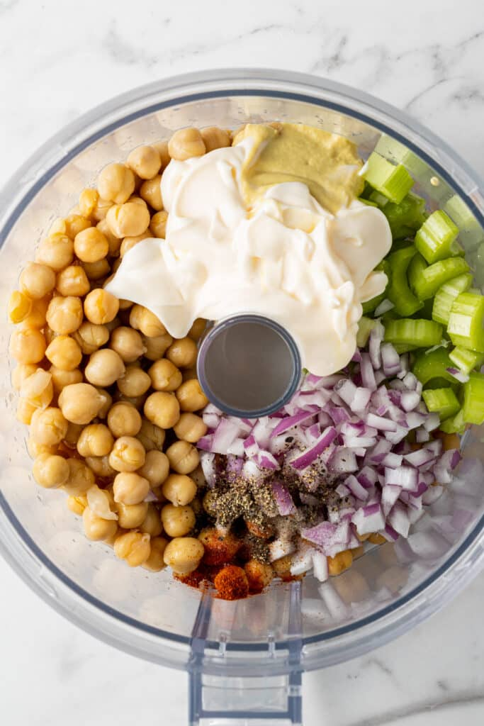 food processor with ingredients to make chickpea salad in it.