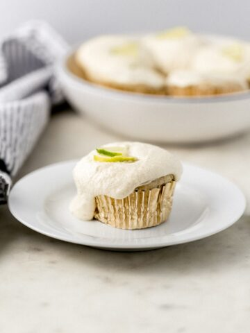 margarita cupcake on small white plate beside cloth napkin with more in the background