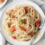 overhead view of pasta and tomato on white plate with fork.