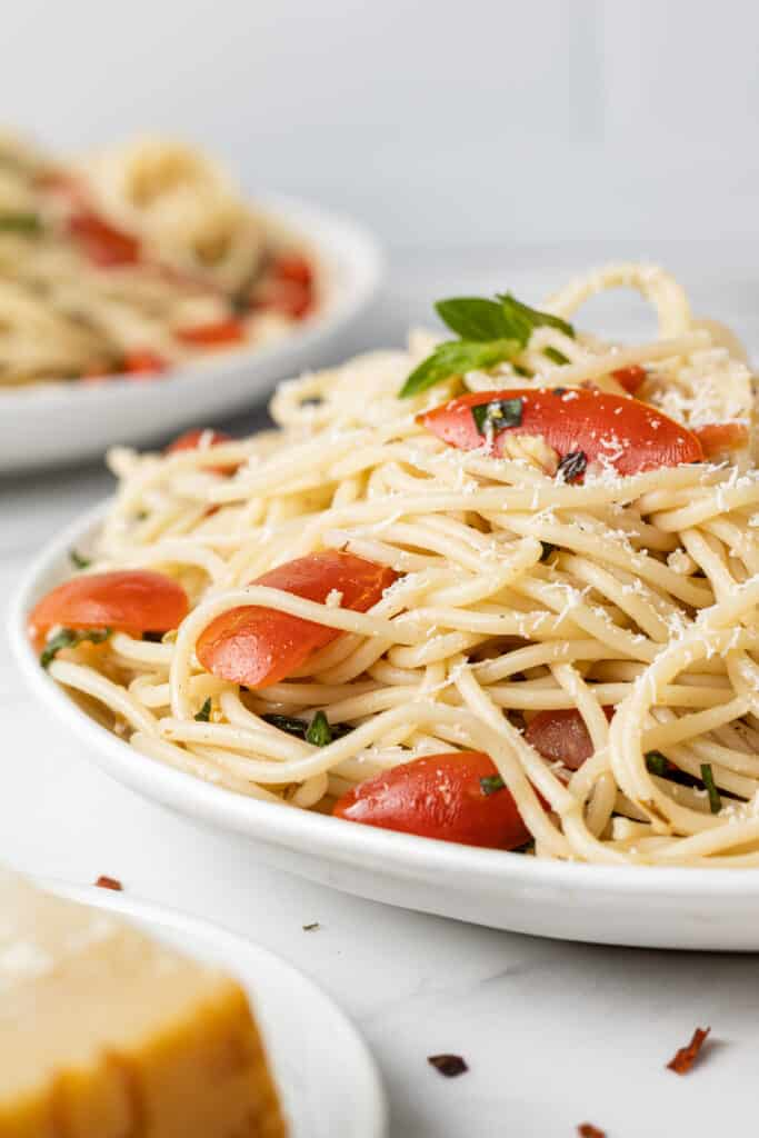 close up side view tomato basil pasta on white plate
