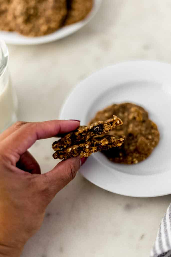 hand holding harvest cookie over white plate with another cookie on it.