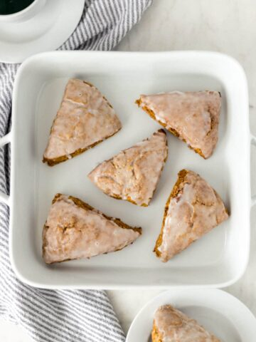 five pumpkin scones on a white dish next to a napkin