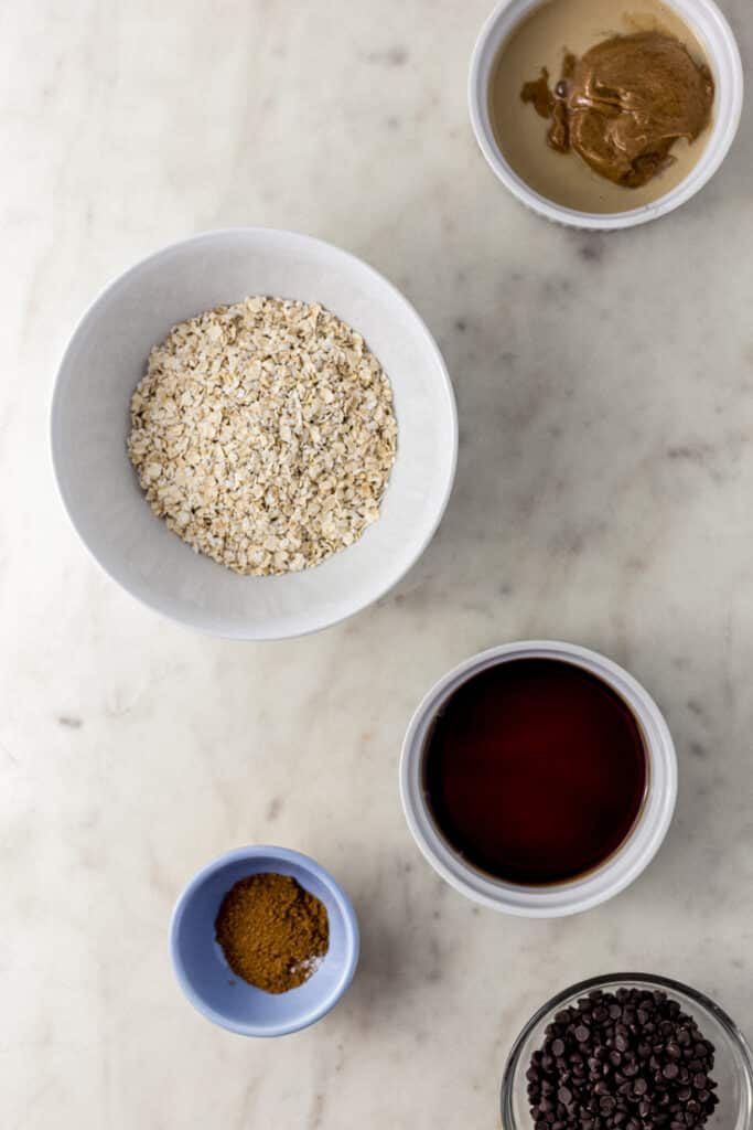ingredients to make tahini cookies in small bowls on marble surface.