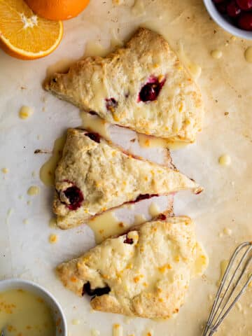 overhead view of three scones on parchment paper with an orange cut in half