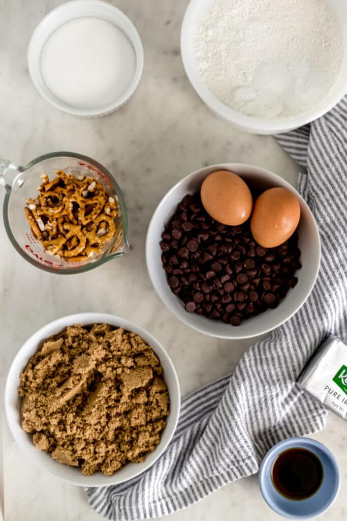 ingredients to make chocolate chip pretzel cookies in separate small bowls and containers.