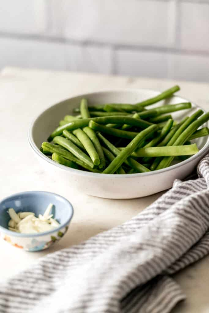 close up side view of fresh green beans and sliced garlic in bowls with napkins
