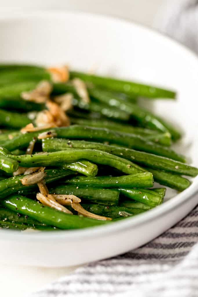 close up side view garlic green beans in a bowl