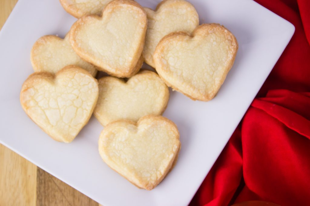 heart shaped shortbread cookies on white plate beside a red cloth napkin