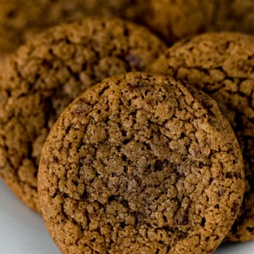 close up side view baked coffee cookies on white plate