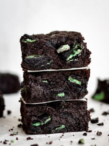 close up side view three square cut fudgy mint brownies stacked on top of each other.